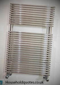 heated towel rail on the wall of tiles