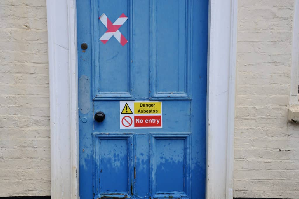 A door with a warning about asbestos